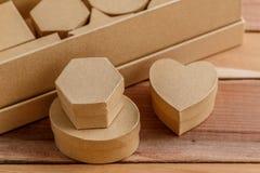 Cajas de cartulina de diversos tamaños y formas en un fondo de madera natural foto de archivo