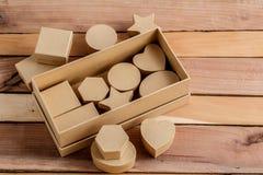 Cajas de cartulina de diversos tamaños y formas en un fondo de madera natural fotografía de archivo libre de regalías