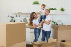 Cajas de desempaque o de embalaje de los pares jovenes felices y que se trasladan a un nuevo hogar fotografía de archivo libre de regalías