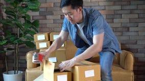 Cajas de embalaje del hombre en casa para la entrega postal almacen de metraje de vídeo