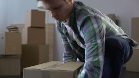 Cajas de embalaje del hombre joven con la materia, moviéndose desde el apartamento, extremo del contrato del alquiler almacen de video