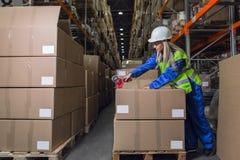 Cajas de embalaje del trabajador de Warehouse en almacén fotografía de archivo
