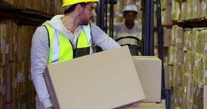 Cajas de embalaje del trabajador de Warehouse en la carretilla elevadora almacen de metraje de vídeo