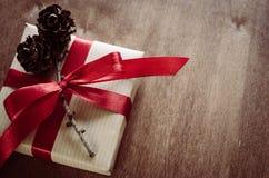 Cajas de Kraft de la Navidad con los regalos, atados con las cintas y los conos rojos del pino en estilo rústico Fotografía de archivo libre de regalías