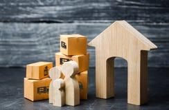 Cajas de la familia y de cartón cerca de la casa El concepto de mudanza a un nuevo hogar, relocalización Mudanza a otra ciudad o  imagen de archivo