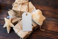 Cajas de la maqueta para los regalos de las etiquetas del papel y del regalo de Kraft en un fondo de madera Imagen de archivo libre de regalías