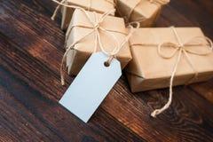 Cajas de la maqueta para los regalos de las etiquetas del papel y del regalo de Kraft en un fondo de madera Fotografía de archivo libre de regalías