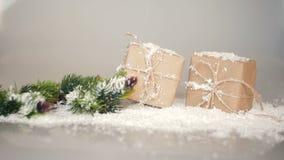 Cajas de la Navidad para los regalos y las ramas en la nieve en un fondo blanco almacen de metraje de vídeo