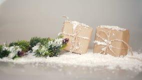 Cajas de la Navidad para los regalos y las ramas en la nieve en un fondo blanco metrajes