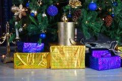 Cajas de regalo amarillas y azules de la Navidad debajo del árbol de pino Imagen de archivo libre de regalías