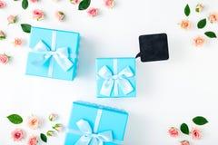 Cajas de regalo azules con las rosas rosadas y la placa de madera negra Imagen de archivo libre de regalías