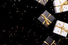 Cajas de regalo blancos y negros con la cinta del oro en fondo del brillo Endecha plana Copie el espacio imagen de archivo libre de regalías