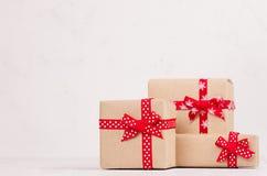 Cajas de regalo brillantes ricas de papel de Kraft con el primer rojo de las cintas en la tabla de madera blanca fotografía de archivo