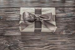 Cajas de regalo de Brown con el arco atado en el tablero de madera del vintage foto de archivo