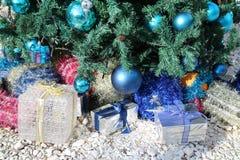 Cajas de regalo coloridas de la Navidad debajo del árbol de navidad adornado con las chucherías y la malla Fotografía de archivo
