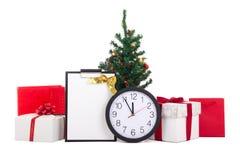 Cajas de regalo con la cinta, el list d'envie, el árbol de navidad y el reloj rojos Imagen de archivo