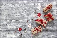 Cajas de regalo con la cinta, las decoraciones de la Navidad y los conos rojos del pino Fotos de archivo