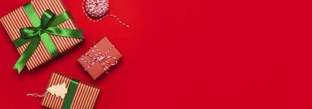 Cajas de regalo con la cinta verde en endecha roja del plano de la opinión superior del fondo El concepto del día de fiesta, el A imagenes de archivo