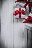 Cajas de regalo con las cintas atadas en concepto de los días de fiesta del tablero de madera Foto de archivo