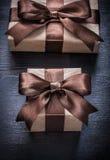 Cajas de regalo con las cintas atadas en el concepto de madera del día de fiesta del tablero Fotografía de archivo libre de regalías