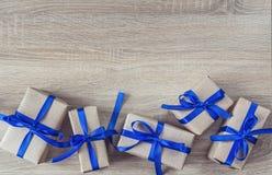 Cajas de regalo con las cintas azules en un fondo de madera y un SP vacío Imagen de archivo
