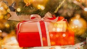 Cajas de regalo con las cintas en un fondo de las luces del bokeh y de las bolas brillantes decorativas de los árboles de pino Imagen de archivo