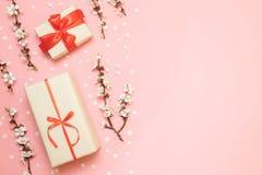Cajas de regalo con las cintas rojas, ramas de la flor fotos de archivo