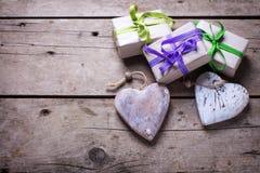 Cajas de regalo con los presentes y corazones decorativos rústicos en w envejecido imágenes de archivo libres de regalías