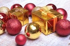 Cajas de regalo con muchas bolas de la Navidad en el fondo de madera Fotos de archivo libres de regalías