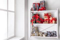 Cajas de regalo de la Navidad en los estantes blancos en el fondo de la pared Imágenes de archivo libres de regalías
