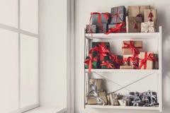 Cajas de regalo de la Navidad en los estantes blancos en el fondo de la pared Fotografía de archivo