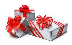 Cajas de regalo de plata aisladas con los arcos rojos Imagenes de archivo