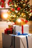 Cajas de regalo debajo del árbol de navidad al lado de la chimenea en la sala de estar Foto de archivo