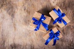 Cajas de regalo del papel reciclado adornado con el lazo de satén azul en el viejo fondo de madera Copie el espacio Imagenes de archivo