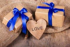 Cajas de regalo del papel reciclado adornado con el lazo de satén azul Tarjeta del día de San Valentín de madera en el viejo fond Fotografía de archivo libre de regalías