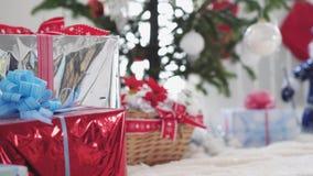 Cajas de regalo elegantes y árbol y Santa Claus borrosos adornados de abeto en el fondo Cámara lenta 3840x2160 metrajes