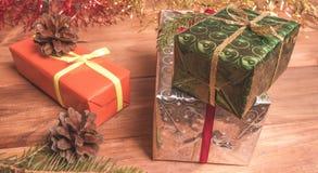 Cajas de regalo entre la malla y los conos de la Navidad Fotos de archivo libres de regalías