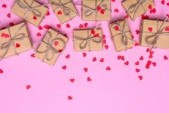 Cajas de regalo envueltas en el documento de Kraft sobre un fondo rosado Corazones del confeti y cintas del oro Foto de archivo libre de regalías