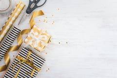 Cajas de regalo envueltas en materiales de papel y de embalaje punteados rayados y de oro blancos y negros en un viejo fondo de m Imágenes de archivo libres de regalías