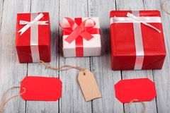 Cajas de regalo hermosas con un arco rojo y blanco en un fondo de madera Fotos de archivo