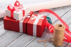 Cajas de regalo hermosas con un arco rojo y blanco en un fondo de madera Imagenes de archivo