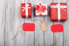 Cajas de regalo hermosas con un arco rojo y blanco en un fondo de madera Imagen de archivo libre de regalías