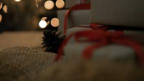 Cajas de regalo de la Navidad con la cinta roja contra fondo de las luces del bokeh del resplandor metrajes