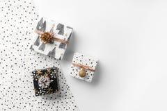 Cajas de regalo de la Navidad en fondo del abrigo con los conos de la decoración y del pino del oro imagen de archivo