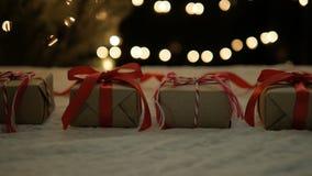 Cajas de regalo de la Navidad en la tela blanca con las luces metrajes