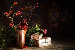 Cajas de regalo de la Navidad entre ramas y escaramujos del abeto en un rusti Imágenes de archivo libres de regalías