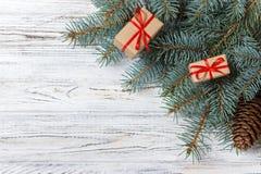 Cajas de regalo de la Navidad y rama de árbol de abeto en la tabla de madera Visión superior con el espacio de la copia Fotografía de archivo libre de regalías