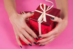 Cajas de regalo rojas del abrazo de la mano de la muchacha aisladas en fondo rosado Imágenes de archivo libres de regalías