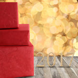 Cajas de regalo rojas y número de madera de 2017 en un piso y un gol de madera Foto de archivo libre de regalías