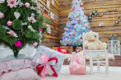 Cajas de regalo, un oso de peluche y dos árboles de navidad dentro de la casa dentro Fotografía de archivo